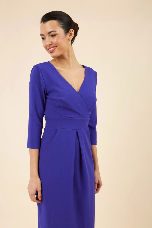 brunette model wearing diva catwalk wimpole a-line flattering dress with lowered v-neck and three quarter sleeve and cinching waistband and widened skirt with pleating in spectrum indigo front