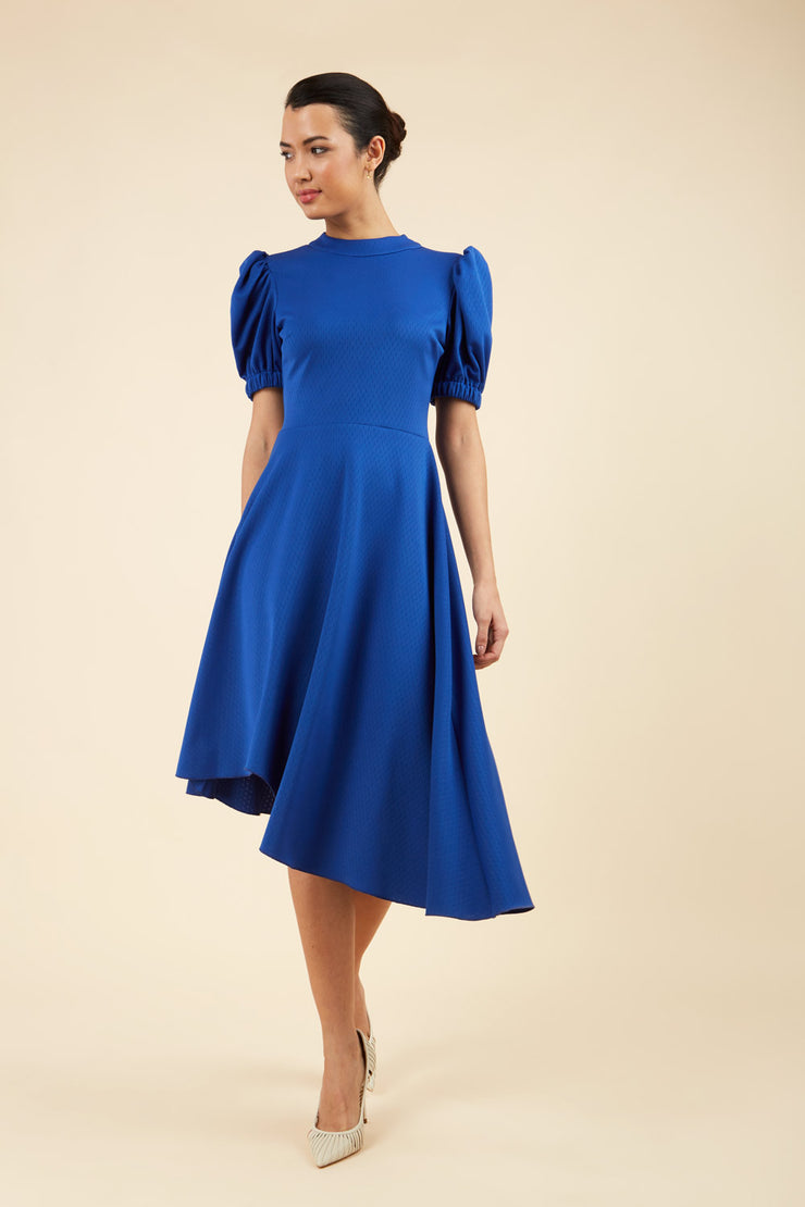 brunette model wearing diva catwalk ola swing dress with puffed oversized sleeves and asymmetric swing skirt with rounded high neck in blue front