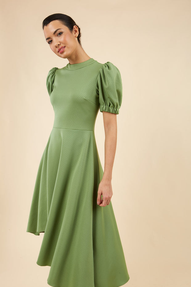brunette model wearing diva catwalk ola swing dress with puffed oversized sleeves and asymmetric swing skirt with rounded high neck in green front