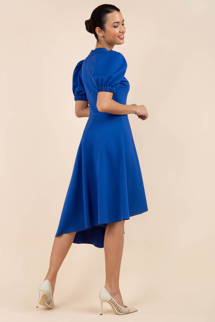 brunette model wearing diva catwalk ola swing dress with puffed oversized sleeves and asymmetric swing skirt with rounded high neck in blue back
