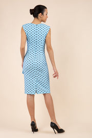 Brunette model wearing Diva Catwalk Perry Polka Dot Pencil Sleeveless Dress with tie detail on a side and rounded neckline in sky blue back