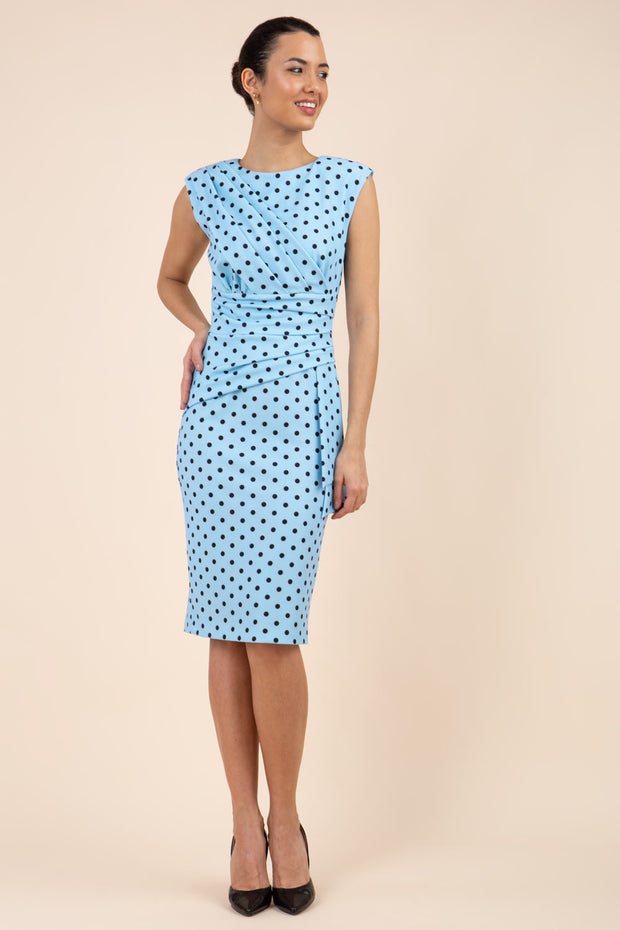 Brunette model wearing Diva Catwalk Perry Polka Dot Pencil Sleeveless Dress with tie detail on a side and rounded neckline in sky blue front