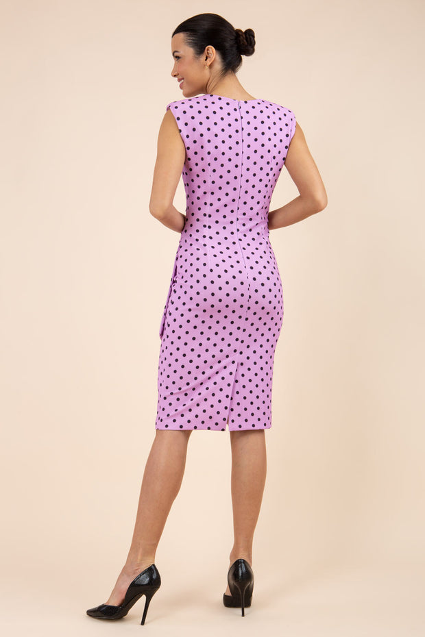 Brunette model wearing Diva Catwalk Perry Polka Dot Pencil Sleeveless Dress with tie detail on a side and rounded neckline in pink back