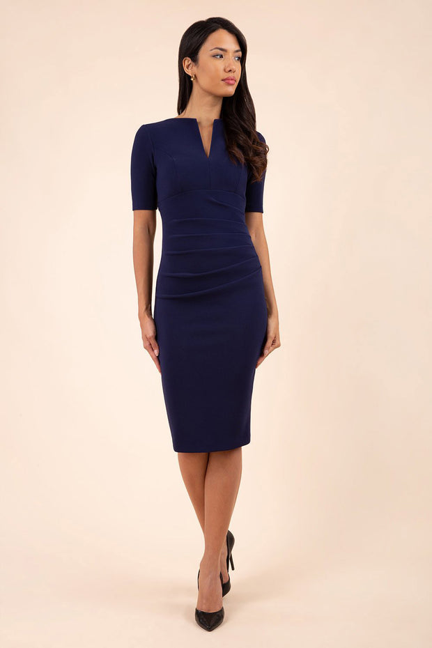blonde model is wearing diva catwalk lydia short sleeve pencil fitted dress in navy blue colour with rounded neckline with a slit in the middle front