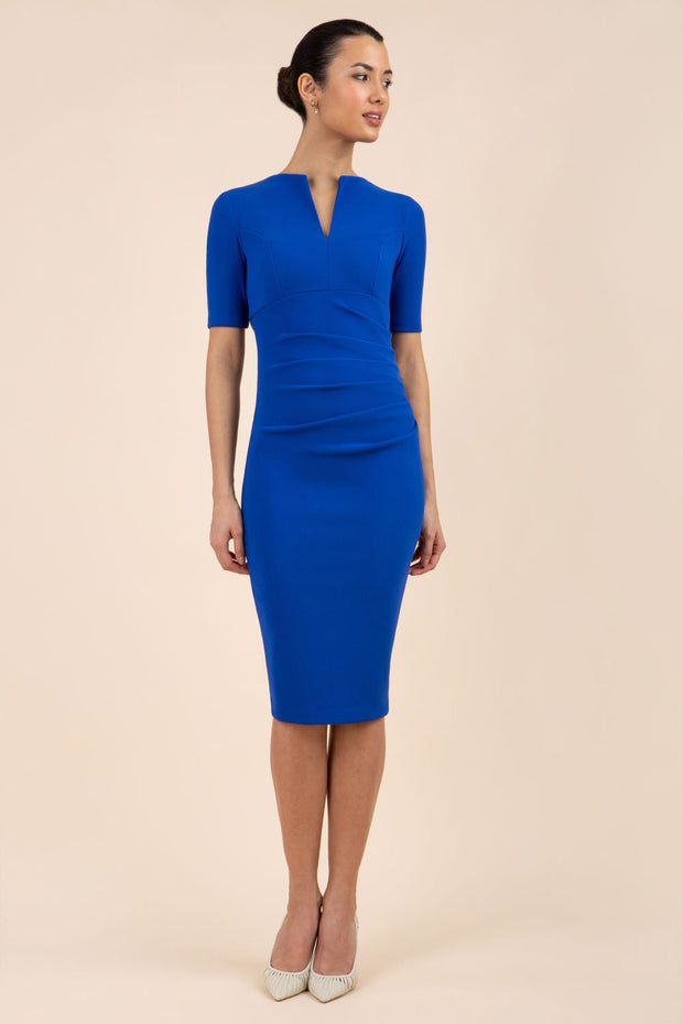 blonde model is wearing diva catwalk lydia short sleeve pencil fitted dress in royal blue colour with rounded neckline with a slit in the middle front