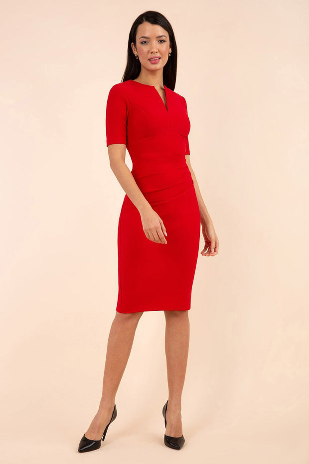 blonde model is wearing diva catwalk lydia short sleeve pencil fitted dress in true red colour with rounded neckline with a slit in the middle front