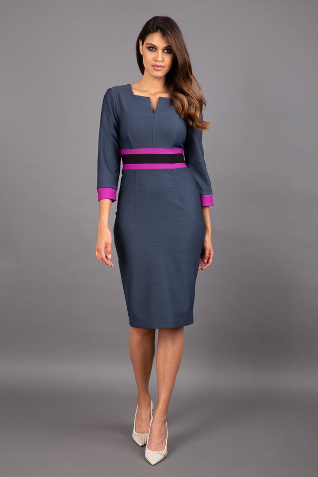 brunette model wearing Diva catwalk Paeonia dress square neckline with a vent in slate grey with dawn purple and black stripes around the waist and three quarter sleeve with dawn purple contrast finish front