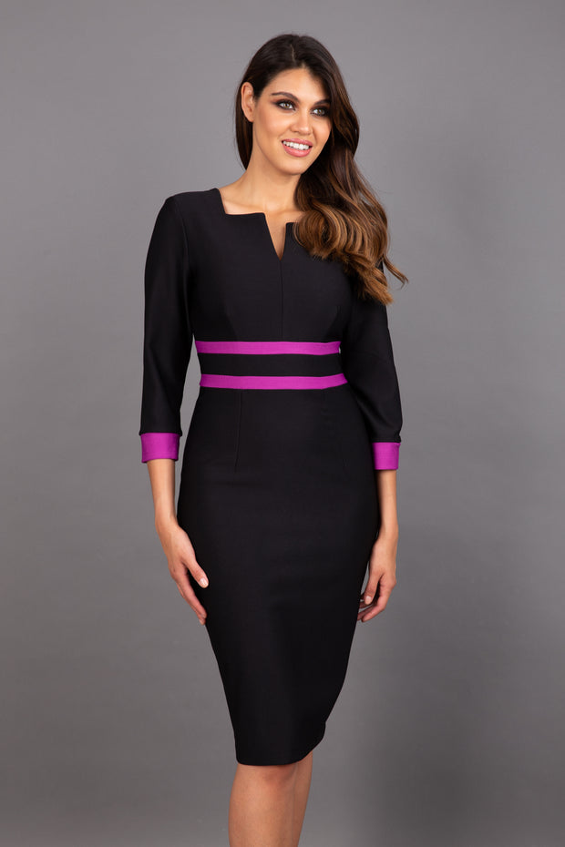 brunette model wearing Diva catwalk Paeonia dress square neckline with a vent in black with dawn purple and black stripes around the waist and three quarter sleeve with dawn purple contrast finish front