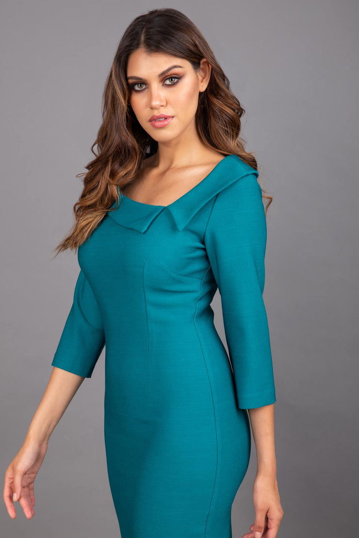 Model wearing Diva catwalk Opulus pencil dress in pacific green with three quarter sleeve figure fitted front image