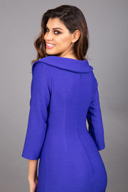 Model wearing Diva catwalk Opulus pencil dress in palace blue with three quarter sleeve figure fitted back image