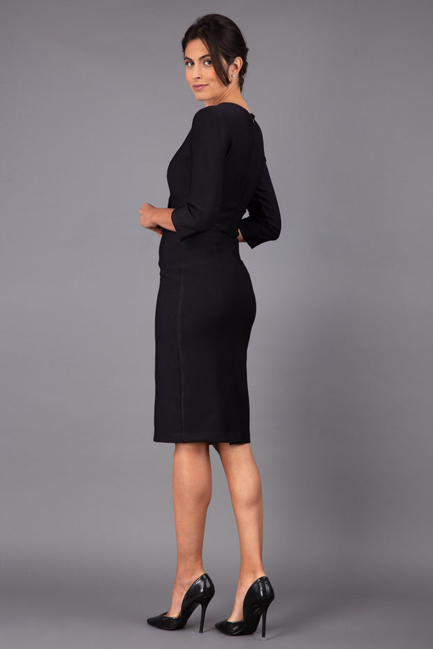 brunette model wearing diva catwalk cranston pencil-skirt dress with low v-neck and tie detail wide band with sleeves in black colour back