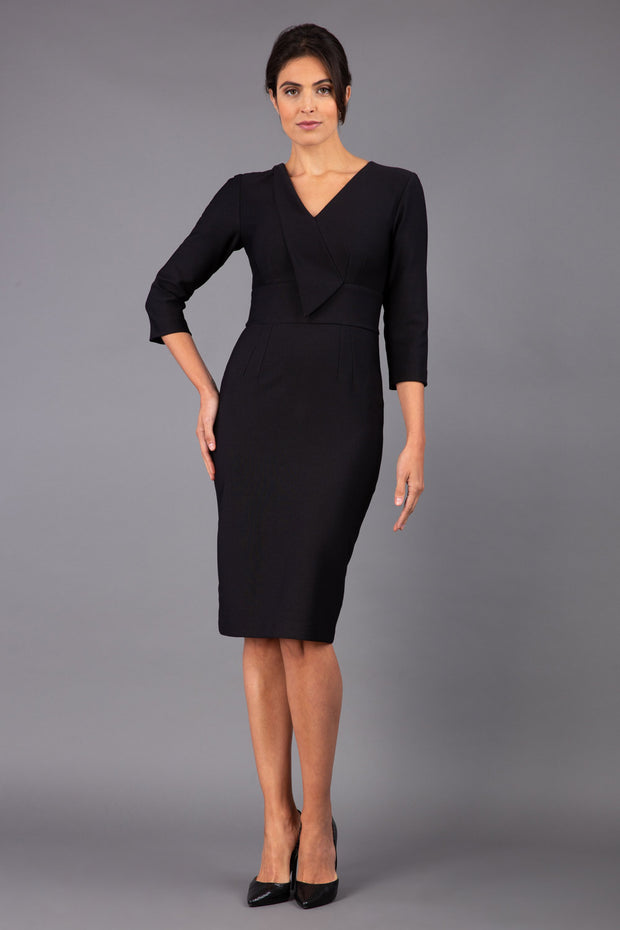 brunette model wearing diva catwalk cranston pencil-skirt dress with low v-neck and tie detail wide band with sleeves in black colour front