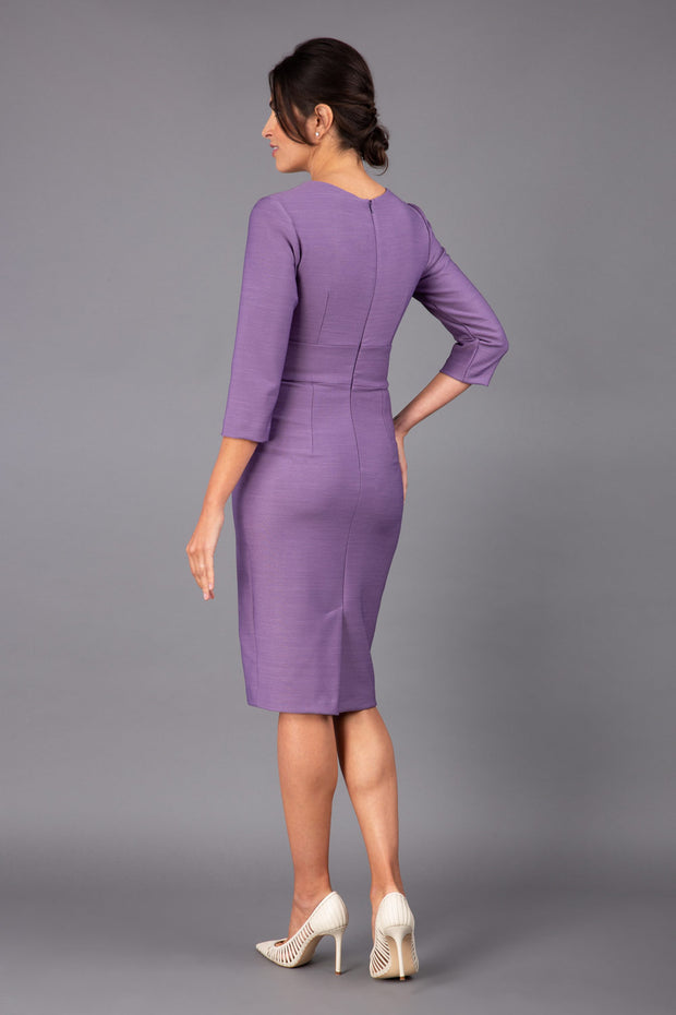 brunette model wearing diva catwalk cranston pencil-skirt dress with low v-neck and tie detail wide band with sleeves in dusty lilac colour back