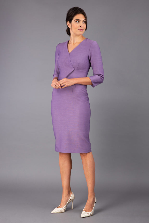 brunette model wearing diva catwalk cranston pencil-skirt dress with low v-neck and tie detail wide band with sleeves in dusty lilac colour front