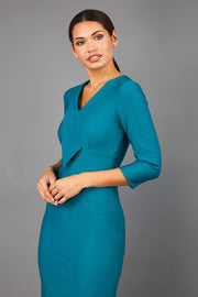 brunette model wearing diva catwalk cranston pencil-skirt dress with low v-neck and tie detail wide band with sleeves in pacific green colour front