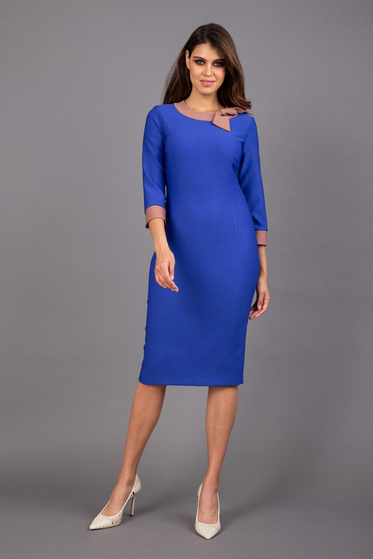 Model wearing Diva catwalk Branwen pencil figure fitted dress in monaco blue with  three quarter sleeve and acorn brown  bow detail  front image