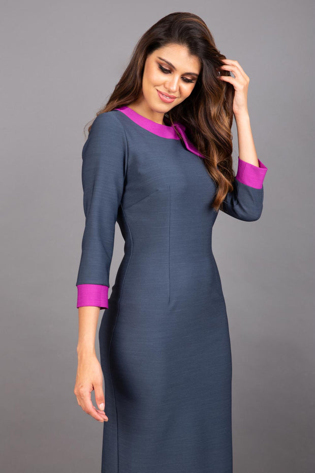 Model wearing Diva catwalk Branwen pencil figure fitted dress in slate grey with three quarter sleeve and dawn purple contrast detail front image