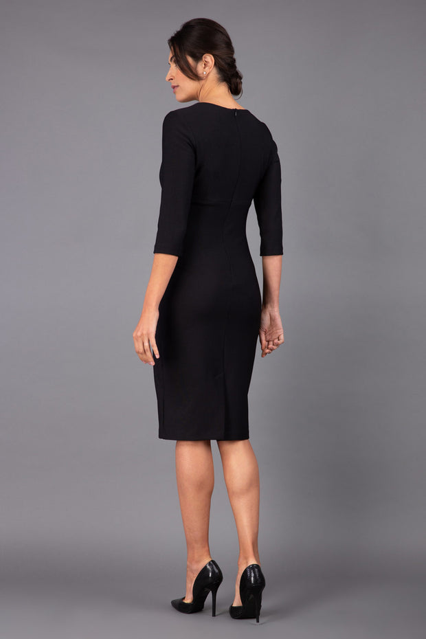 Model wearing Diva catwalk Minette dress in black with three quarter sleeve figure fitted pencil dress back image