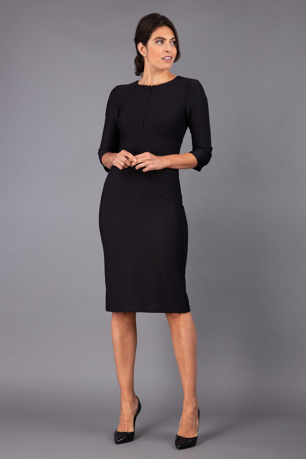 Model wearing Diva catwalk Minette dress in black with three quarter sleeve figure fitted pencil dress front image