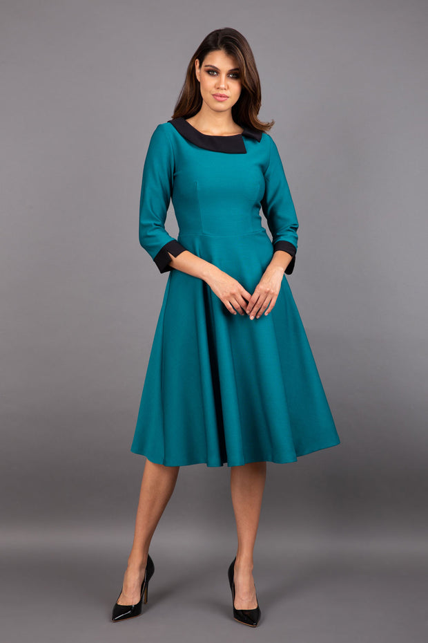 Model wearing Diva catwalk Coralia swing dress in pacific green with three quarter sleeve figure fitted front image