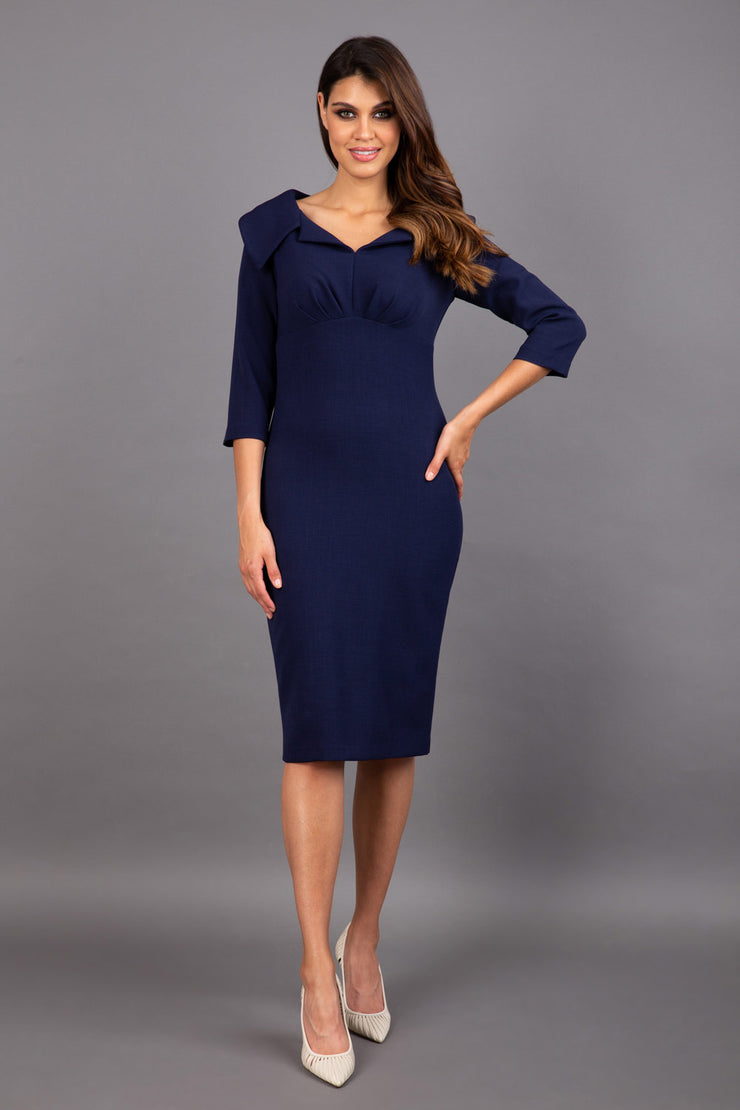 Model wearing Diva catwalk Venetia pencil figure fitted dress in navy blue with three quarter sleeve front