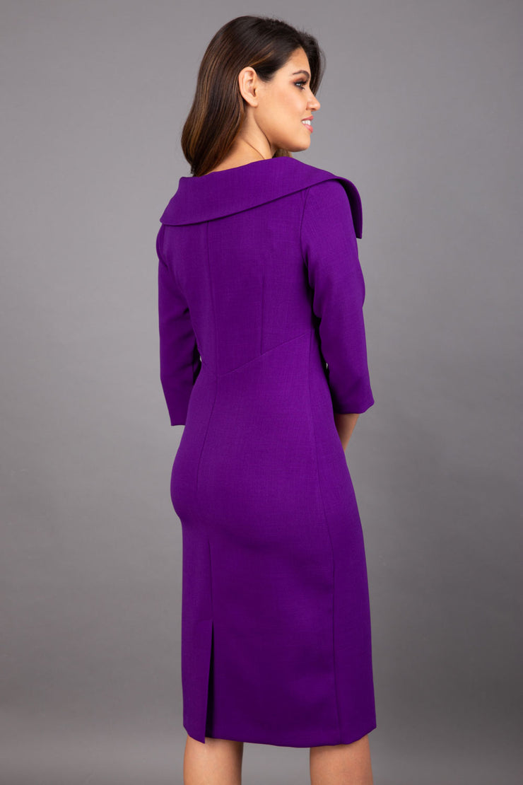 Model wearing Diva catwalk Venetia pencil figure fitted dress in deep purple with three quarter sleeve back