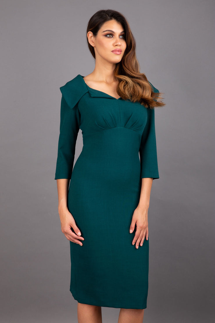 Model wearing Diva catwalk Venetia figure fitted pencil dress in forest green with three quarter sleeve front
