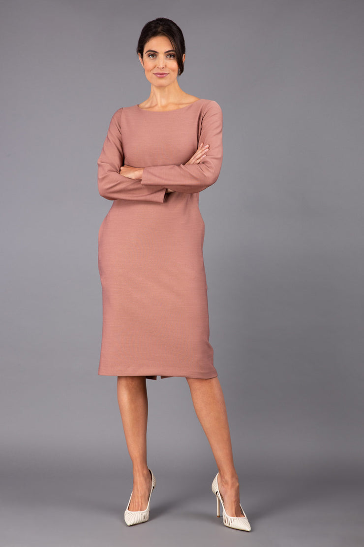 brunette model wearing diva catwalk cora white pencil dress with long sleeves and rounded neckline with pockets in colour acorn brown on side front
