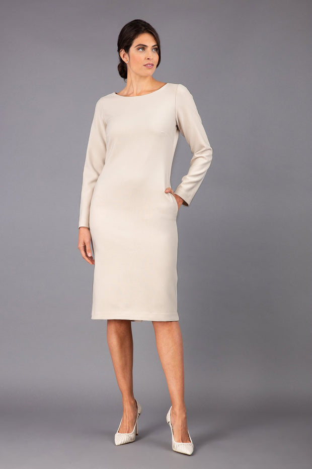 brunette model wearing diva catwalk cora white pencil dress with long sleeves and rounded neckline with pockets in colour cream on side front