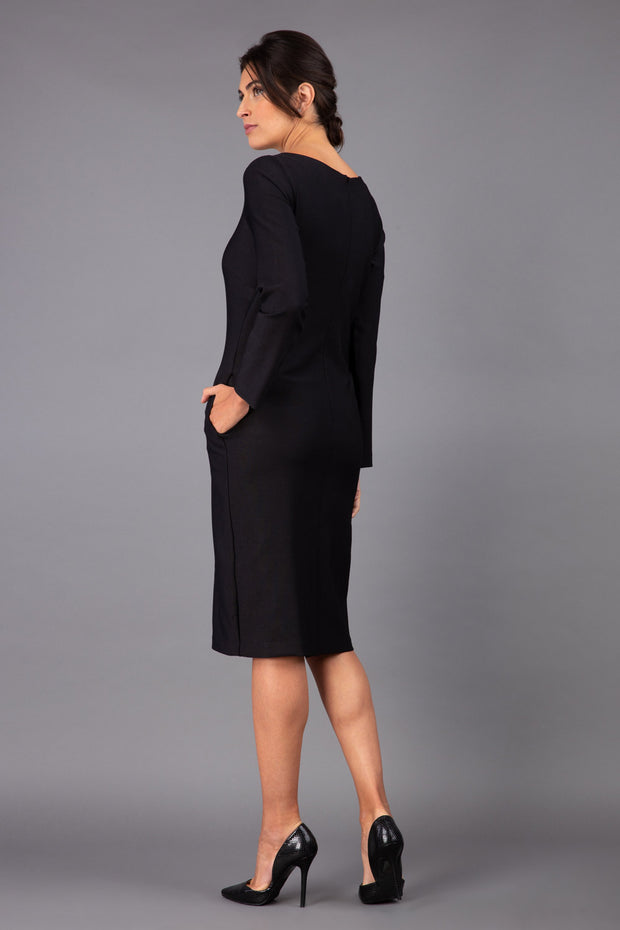 brunette model wearing diva catwalk cora white pencil dress with long sleeves and rounded neckline with pockets in colour black on side back