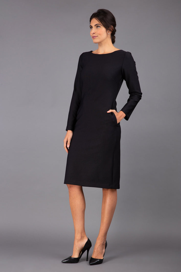 brunette model wearing diva catwalk cora white pencil dress with long sleeves and rounded neckline with pockets in colour black on side front