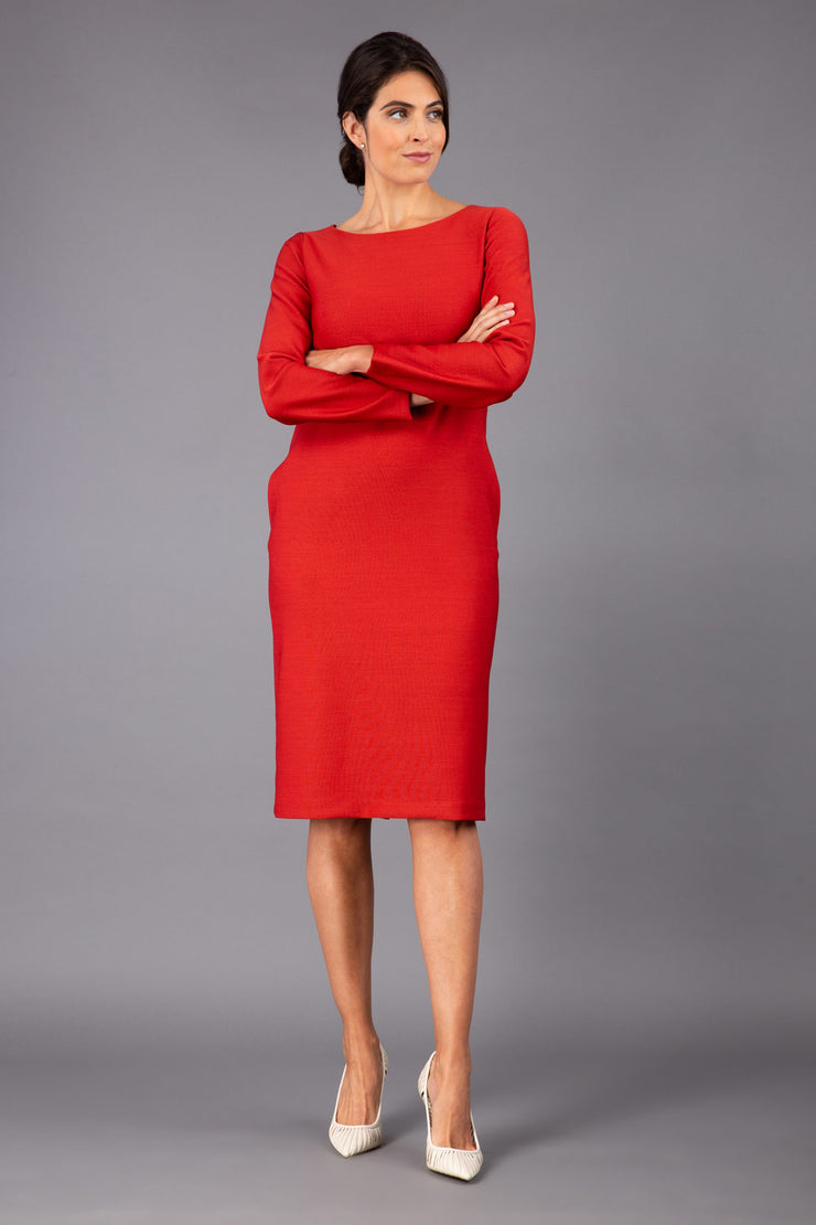 brunette model wearing diva catwalk cora white pencil dress with long sleeves and rounded neckline with pockets in colour red on side front