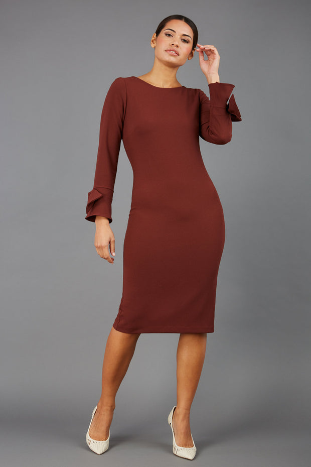 brunette model wearing diva catwalk fitted dress with sleeves called Alma Pencil-skirt dress in colour mahogany brown with bow detail on sleeves front