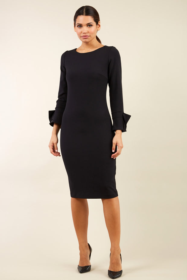 brunette model wearing diva catwalk fitted dress with sleeves called Alma Pencil-skirt dress in colour black with bow detail on sleeves front
