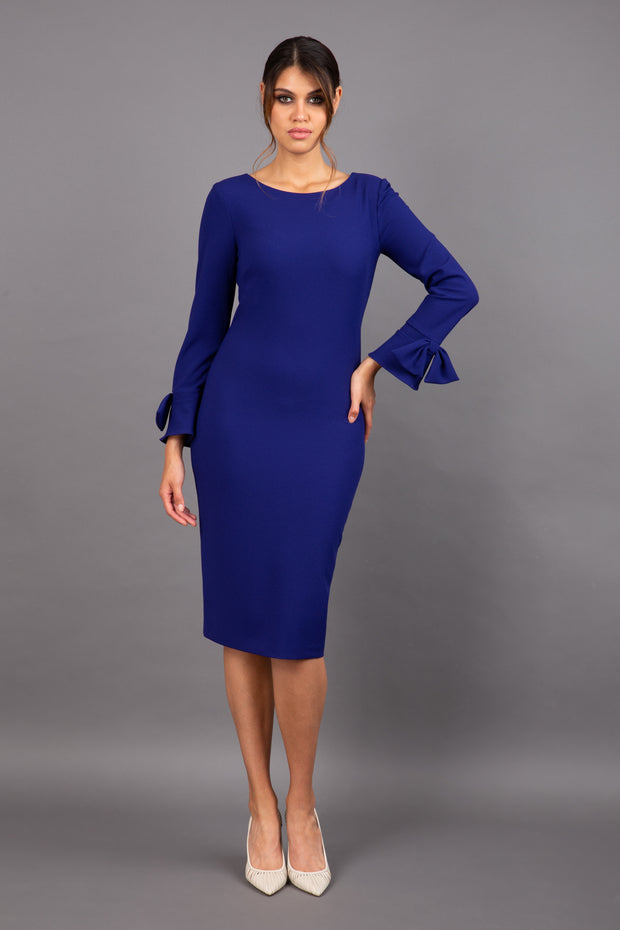 brunette model wearing diva catwalk fitted dress with sleeves called Alma Pencil-skirt dress in colour oxford blue with bow detail on sleeves front