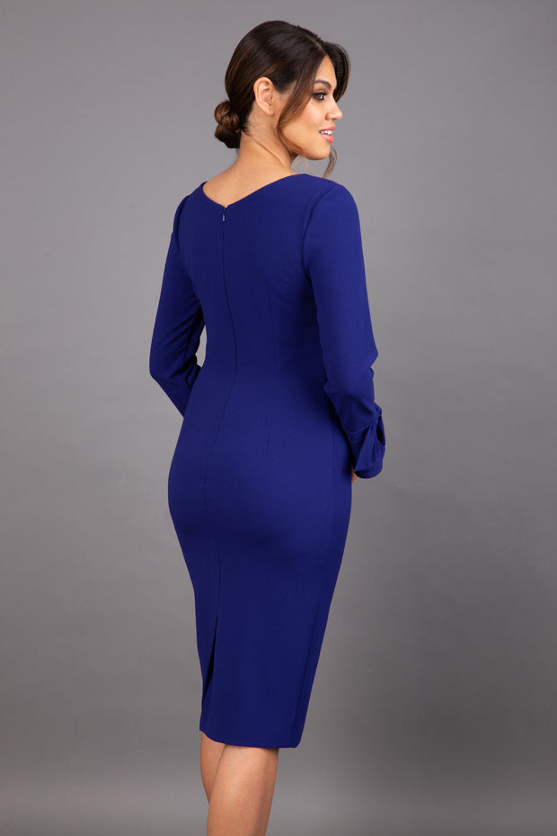 brunette model wearing diva catwalk fitted dress with sleeves called Alma Pencil-skirt dress in colour oxford blue with bow detail on sleeves back