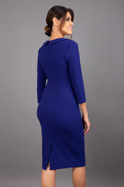 brunette model wearing diva catwalk elodie pencil fitted dress with rounded neckline and button detail and three quarter sleeve with pleating across the body from side triangle detail in oxford blue back