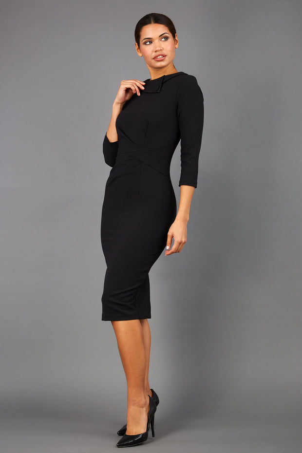 brunette model wearing diva catwalk elodie pencil fitted dress with rounded neckline and button detail and three quarter sleeve with pleating across the body from side triangle detail in blackfront