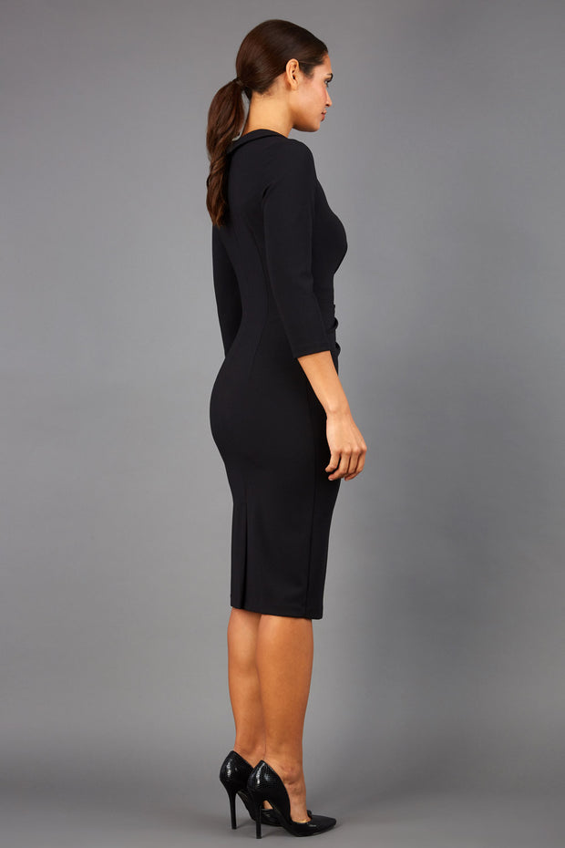 brunette model wearing diva catwalk elodie pencil fitted dress with rounded neckline and button detail and three quarter sleeve with pleating across the body from side triangle detail in black back