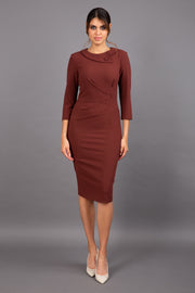 brunette model wearing diva catwalk elodie pencil fitted dress with rounded neckline and button detail and three quarter sleeve with pleating across the body from side triangle detail in mahogany front