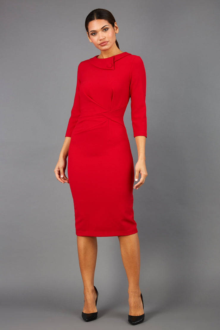 brunette model wearing diva catwalk elodie pencil fitted dress with rounded neckline and button detail and three quarter sleeve with pleating across the body from side triangle detail in scarlet red front