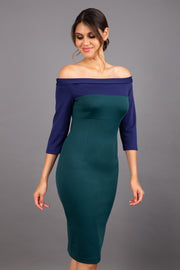 brunette model wearing diva catwalk leon pencil contrast dress with boat off shoulder fold over neckline and three quarter sleeve and empire waistline in forest green and navy blue front
