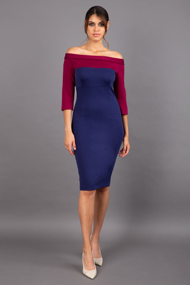 brunette model wearing diva catwalk leon pencil contrast dress with boat off shoulder fold over neckline and three quarter sleeve and empire waistline in navy blue and blissful burgundy front