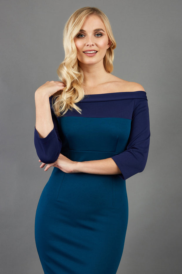 blonde model wearing diva catwalk leon pencil contrast dress with boat off shoulder fold over neckline and three quarter sleeve and empire waistline in teal and navy blue front