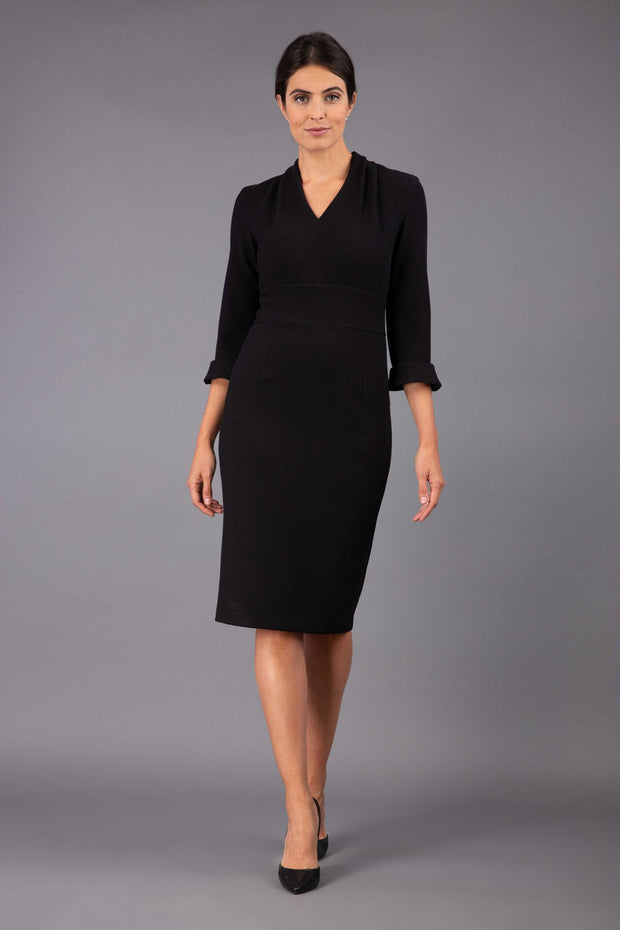 brunette model wearing diva catwalk adriana pencil dress with low v-neck and pleating around shoulders with three quarter sleeve detailed on end and wide waistband in black front
