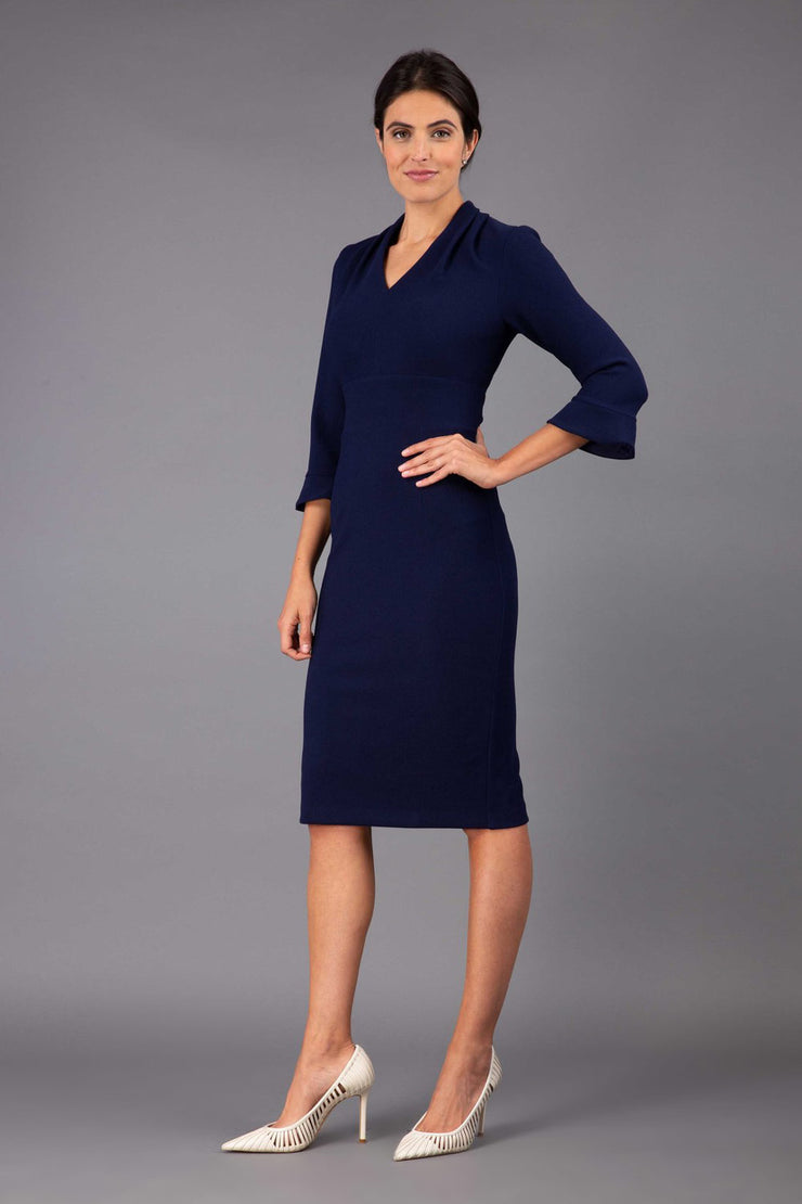 brunette model wearing diva catwalk adriana pencil dress with low v-neck and pleating around shoulders with three quarter sleeve detailed on end and wide waistband in dark navy front