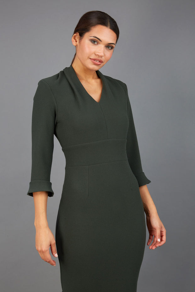 brunette model wearing diva catwalk adriana pencil dress with low v-neck and pleating around shoulders with three quarter sleeve detailed on end and wide waistband in obsidian green front