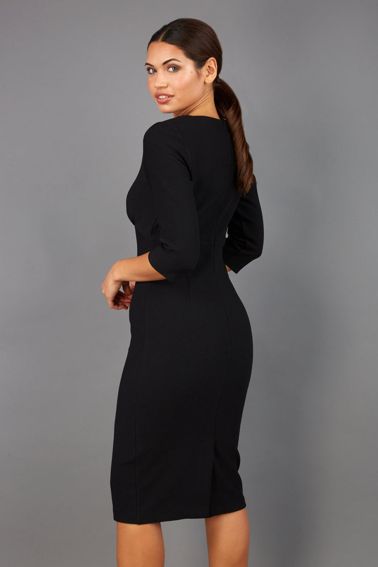 Brunette model wearing Diva Catwalk Lovell Pencil Dress in black  with lowered sweetheart neckline and three quarter sleeve with gathering at the bust back