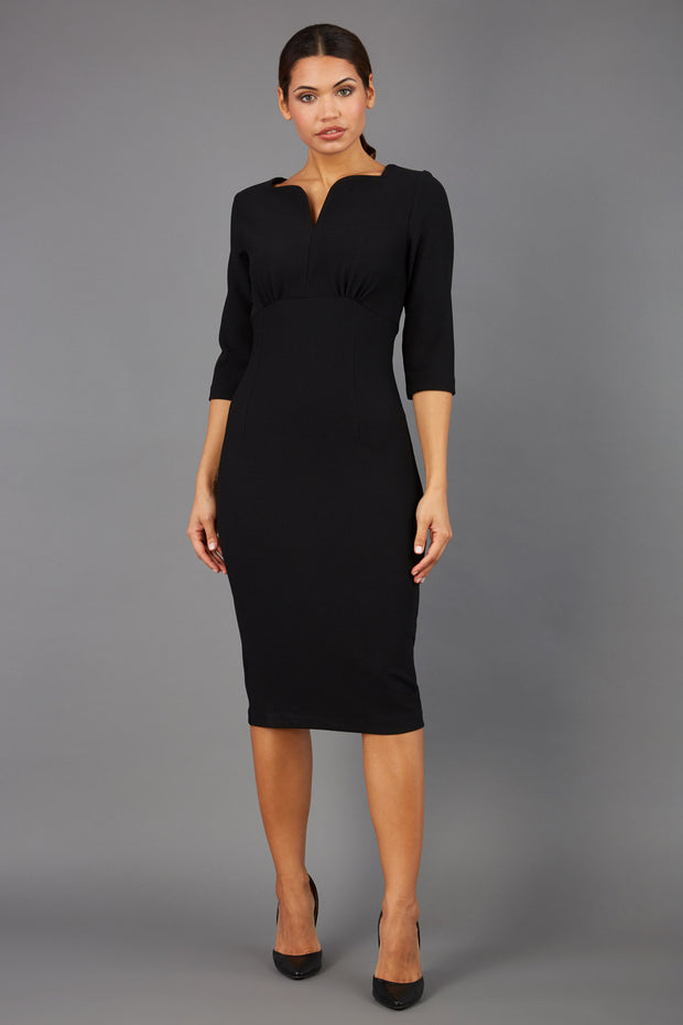 Brunette model wearing Diva Catwalk Lovell Pencil Dress in black  with lowered sweetheart neckline and three quarter sleeve with gathering at the bust front