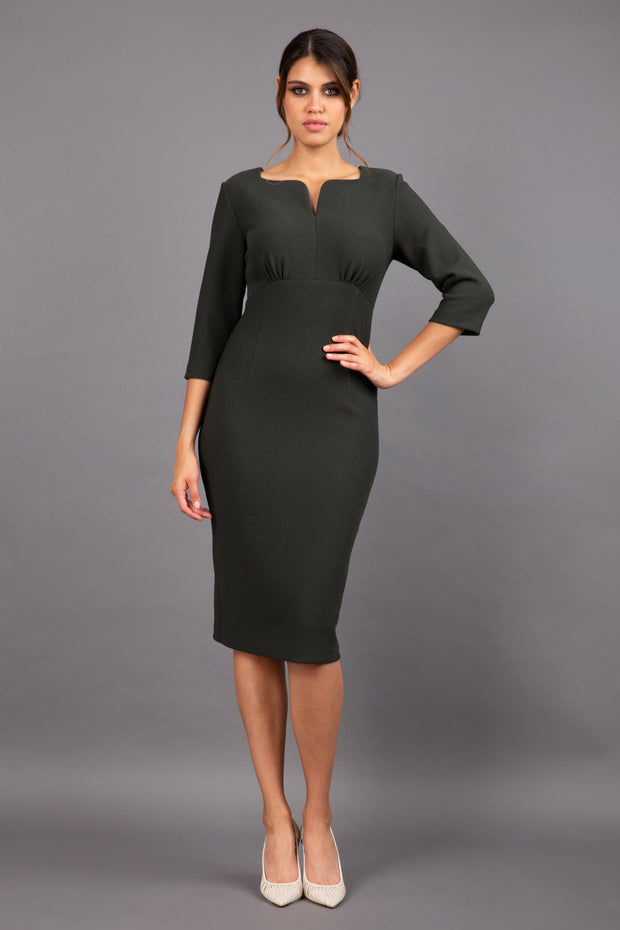 Brunette model wearing Diva Catwalk Lovell Pencil Dress in Obsidian Green with lowered sweetheart neckline and three quarter sleeve with gathering at the bust front